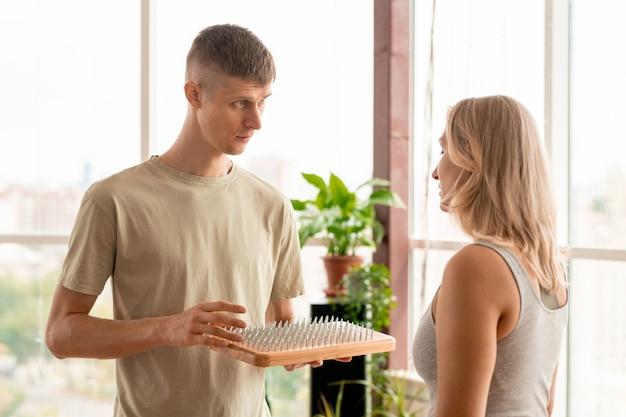 Молодая блондинка в спортивной одежде слушает рекомендации личного тренера по йоге о тренировках с массажной подушкой