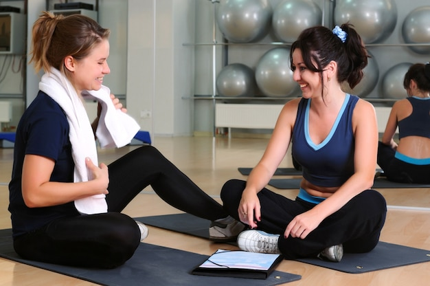 Young blond fitness trainer helps to brunette woman doing physical exercise at gym