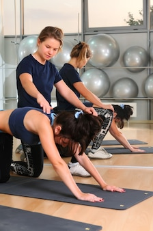 Young blond fitness trainer in sportswear helps to brunette woman doing push ups on yoga mat at gym