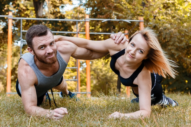 Young blond girl and bearded man doing exercise plank at sunny autumn day in park.