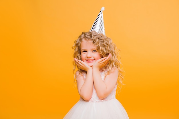 Young blond girl in birthday party princess hat hands spread up screaming