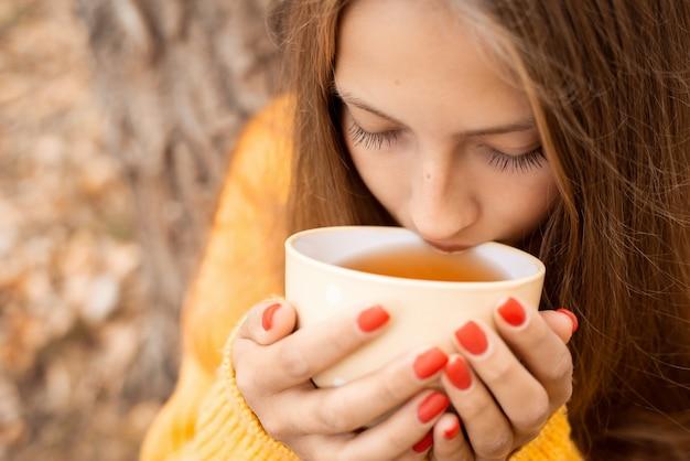 자신을 따뜻하게 하기 위해 큰 흰색 컵에서 녹차를 마시는 젊은 금발 소녀. 가을 시간, 아늑한 순간, 야외에서 시간을 보내는 것.