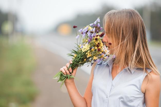 若いブロンドの女の子は、野生の花の花束の香りを楽しんでいます。