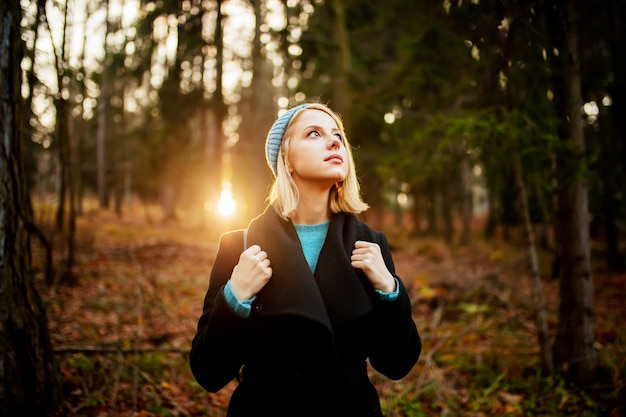 Young blond girl in a forest in sunset time
