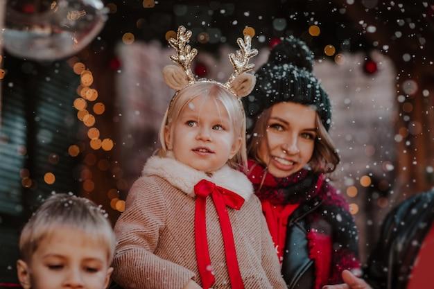 冬のコートを着た若いブロンドの女の子と彼女の家族の間でポーズをとる鹿の角のようなヘッドバンド