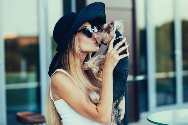 작은 개를 키스하는 젊은 금발 소녀