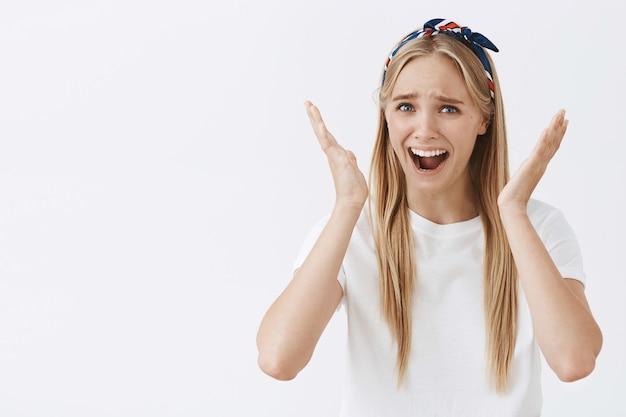Молодая блондинка позирует у белой стены