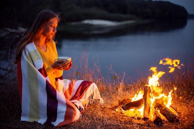 川岸のキャンプファイヤーの近くに座って何かを夢見ている若いブロンドの女の子