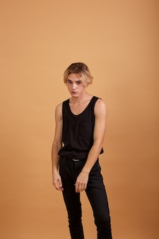 Young blond guy dressed in a black t-shirt and pants posing in the studio on the beige background .
