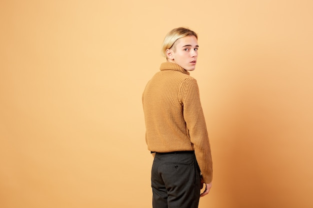 Young blond guy dressed in mustard color sweater and black pants is posing in the studio on the beige background .