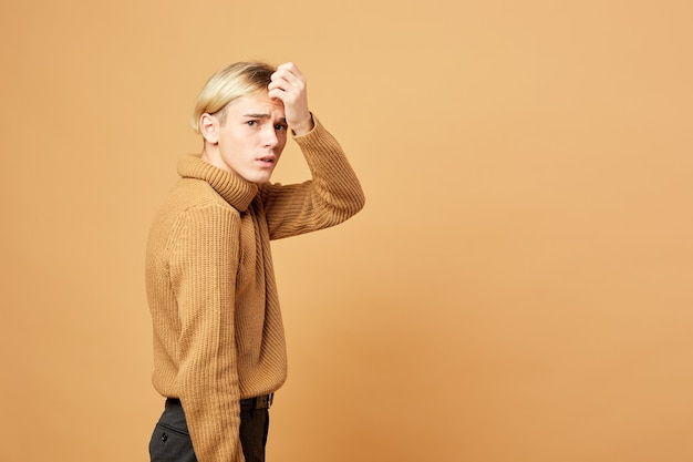 Young blond guy dressed in mustard color sweater and black pants is posing with his hand on his forehead in the studio on the beige background .