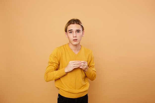 Young blond guy dressed in yellow sweater is posing in the studio on the beige background .