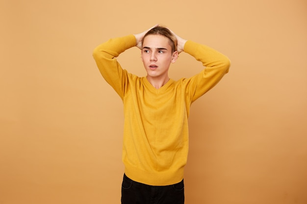 Young blond guy dressed in yellow sweater keeps his hands on his head on the beige background in the studio .