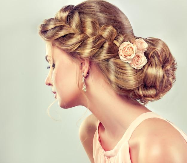 彼女の頭を囲む広いひだと彼女の顔に鮮やかなメイクでファッショナブルなエレガントな結婚式や夜の髪型を持つ若いブロンドの髪の女性