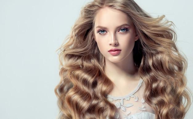 ボリュームのある髪の若い、ブロンドの髪の女性。ゆったりとしたカールと鮮やかなメイクでスタイリッシュでルーズなヘアスタイルの美しいモデル。飛んでいる髪。