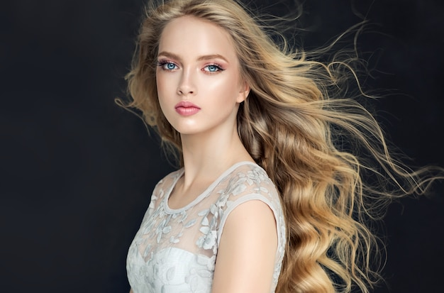 Young, blond haired woman with voluminous hair. beautiful model with stylish, loose hairstyle with freely lying curls and vivid makeup. flying hair.