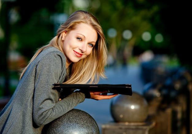 Молодая белокурая счастливая коммерсантка в официальной одежде, стоя с документами в парке в летний ясный день. концепция красивая современная бизнесвумен