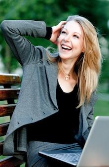 Молодая блондинка дама в официальной деловой одежде сидит на скамейке в парке с ноутбуком и ветром в волосах в летний ясный день. концепция красивая современная бизнесвумен