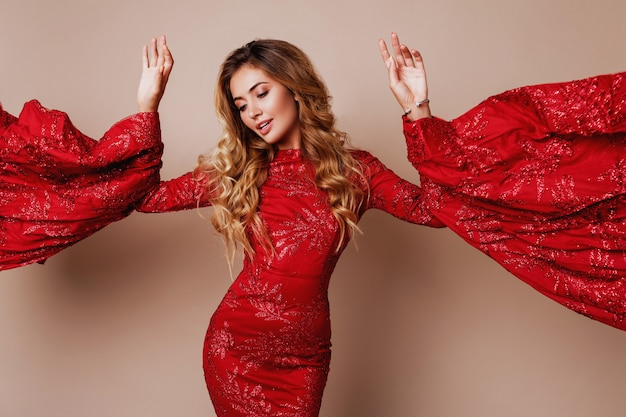 Young blond lovely woman in luxurious red dress with wide sleeves. expressive pose.