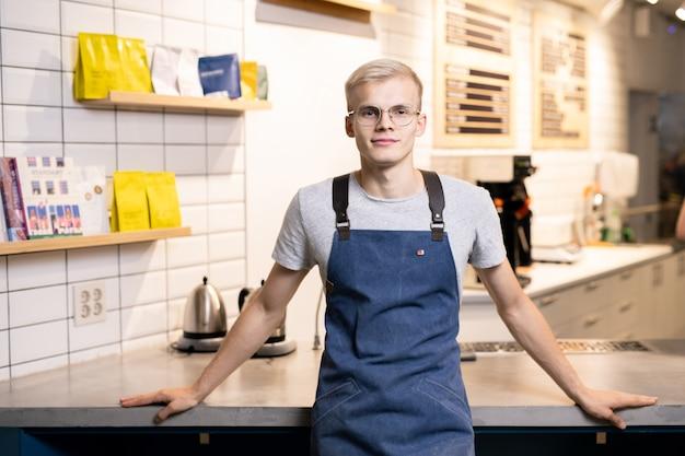 Молодой блондин в очках, фартуке и повседневной одежде смотрит на вас у своего рабочего места в кафе или ресторане