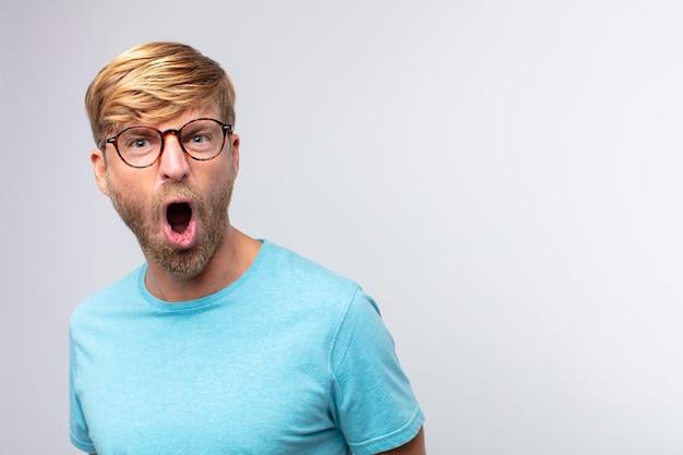 Молодой блондин кричит и сердится