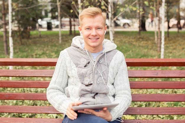 Молодой белокурый человек сидит и слушает музыку с наушниками и планшетом, концепция образа жизни