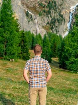若いブロンドの男は、ドロミテ、イタリアの山々を見下ろす緑の芝生の上に立っています