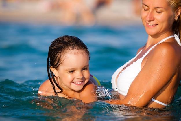 푸른 비키니를 입은 젊은 금발 어머니가 물 속에 서서 여름날 햇살 아래 웃고 있는 작은 딸을 수영하는 것을 돕습니다. 가족 휴가 및 여행 개념