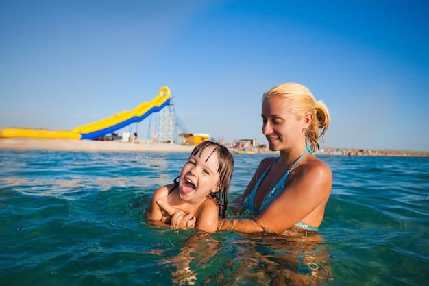 水に立って、彼女の小さな笑顔の娘を泳ぐのを手伝って青いビキニの若いブロンドの母親