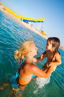 물에 서서 그녀의 작은 웃는 딸과 함께 노는 파란색 비키니 입은 젊은 금발 어머니