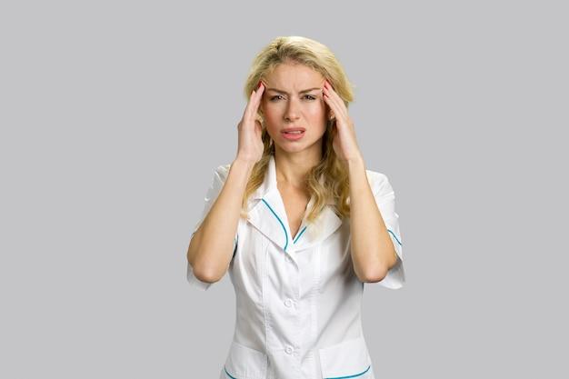 Молодая блондинка медсестра, имеющая головную боль