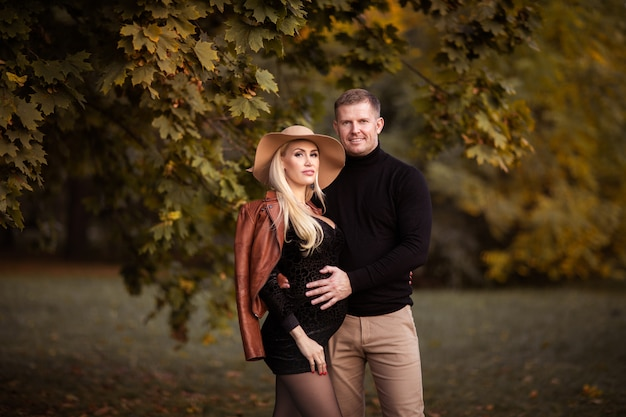 Young blond pregnant woman posing with man at the autumn.