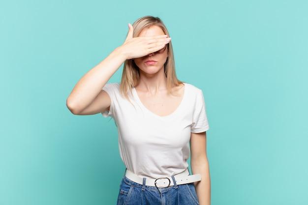 片手で目を覆っている若い金髪のきれいな女性は、恐怖や不安を感じ、不思議に思ったり、盲目的に驚きを待っています