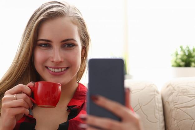 若いブロンドのきれいな女性のコーヒーを飲むとソファに座っている朝のラップトップを見て