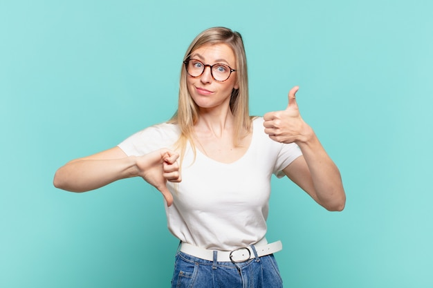 若い金髪のきれいな女性は、混乱し、無知で、確信が持てず、さまざまなオプションや選択肢で良い点と悪い点に重みを付けています