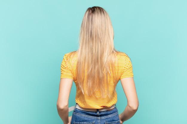 젊은 금발의 예쁜 여성은 혼란스럽거나 가득 차거나 의심과 질문을 느끼고 엉덩이에 손을 얹고 후면 보기