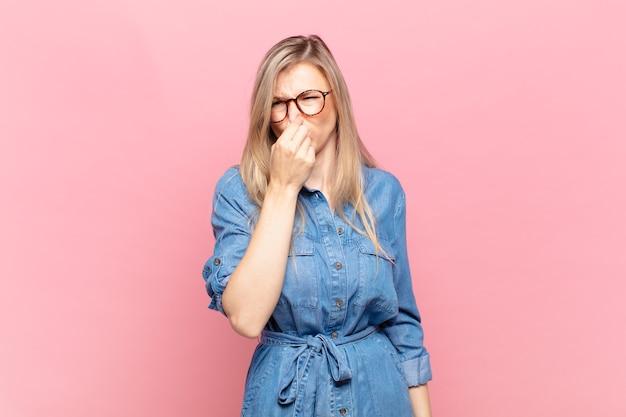 젊고 금발의 예쁜 여자는 역겨움을 느끼고, 더럽고 불쾌한 냄새를 피하기 위해 코를 잡고 있다