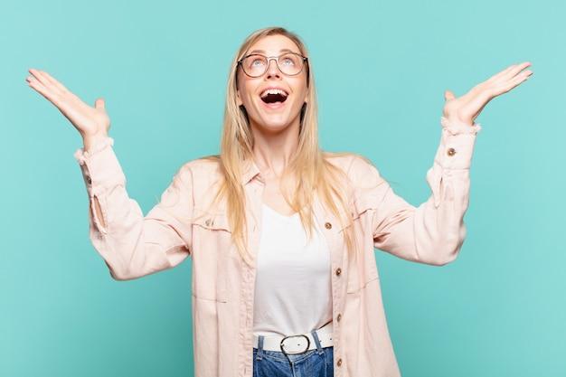 幸せ、驚き、幸運、驚きを感じ、空中で両手を上げて勝利を祝う若い金髪のきれいな女性