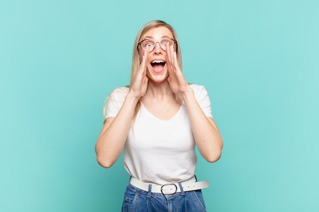 幸せ、興奮、前向きな気持ちで、口の横に手を置いて大きな叫び声を上げ、声をかける若い金髪のきれいな女性