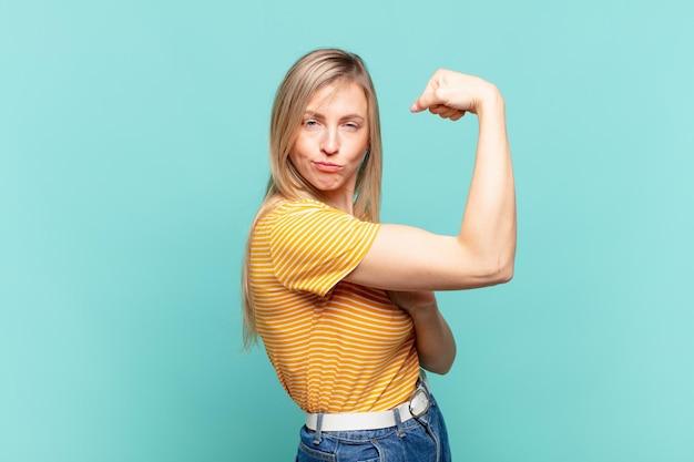 幸せ、満足、パワフル、屈曲フィットと筋肉の上腕二頭筋を感じ、ジムの後に強く見える若い金髪のきれいな女性