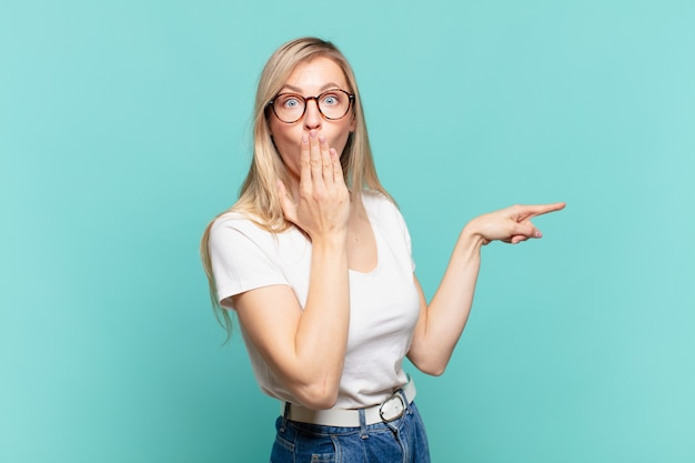 Young blond pretty woman feeling happy, shocked and surprised, covering mouth with hand and pointing to lateral copy space
