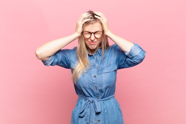 若い金髪のきれいな女性は、ストレスと欲求不満を感じ、手を頭に上げ、疲れ、不幸、片頭痛を感じています