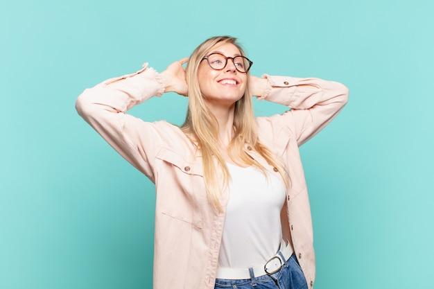 젊고 금발의 예쁜 여자가 웃고 편안하고 만족하며 근심하지 않고 긍정적으로 웃고 차가워집니다.