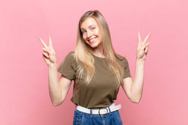 若い金髪のきれいな女性は笑顔で幸せそうに見え、友好的で満足し、両手で勝利または平和を身振りで示す