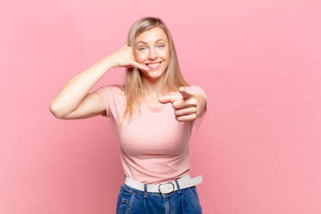 Молодая белокурая красивая женщина, весело улыбаясь и указывая на камеру, звоня вам позже жестом, разговаривает по телефону