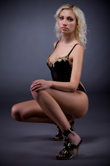Young blond slim woman in sexy black lingerie and high heeled shoes sitting and looking above over dark background in photo studio. beauty of woman body and stylish underwear concept