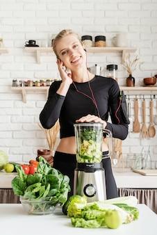음악을 듣고 집 부엌에서 녹색 스무디를 만드는 검은 sportwear에 젊은 금발 웃는 여자