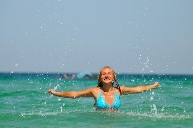 晴れた晴れた夏の日に立って、水中にいることを楽しんでいる青いビキニの若い金髪の笑顔の女性。幸福、休暇、自由の概念