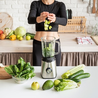 Young blond smiling woman making green smoothie at home kitchen
