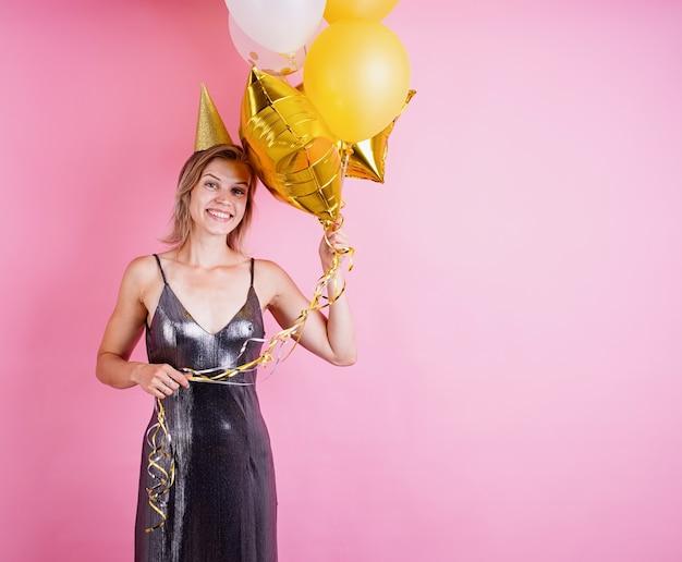 복사 공간 분홍색 배경에 생일을 축하하는 황금 풍선을 들고 생일 모자를 쓰고 젊은 금발 웃는 여자